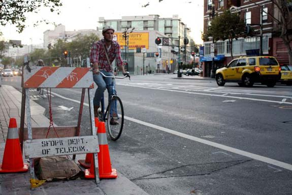 A bicyclist approaches a new bike counter on Market Street just west of Van Ness Avenue.