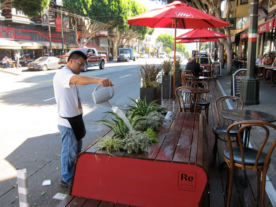 An employee of Cafe Greco waters the plants on the new parklet. All maintenance of the parklet is the responsibility of the property owner.